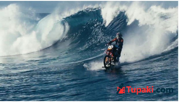 Surfing ocean waves on a dirt bike