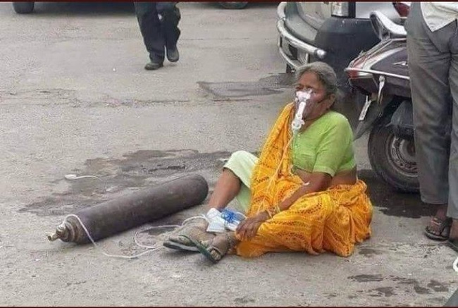 An old woman with an oxygen cylinder on the road